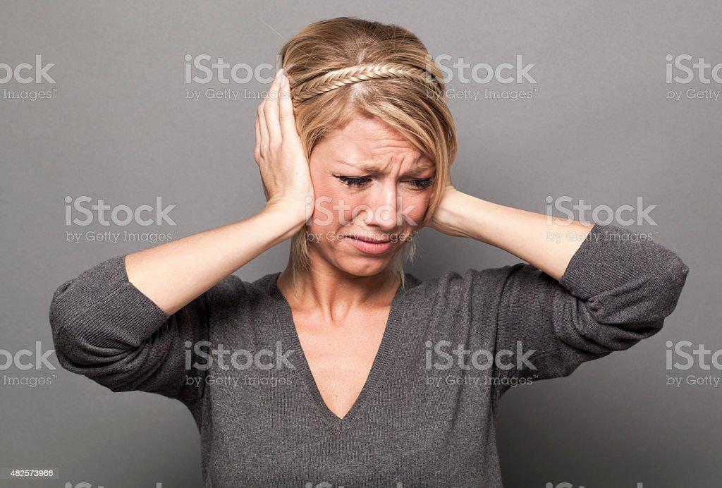 20's blonde girl in pain, suffering from headache, avoiding noise stock photo