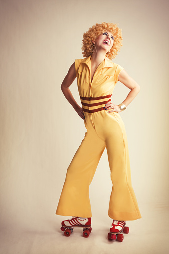 A retro 70's woman wearing a bell bottom jumpsuit and roller skates.