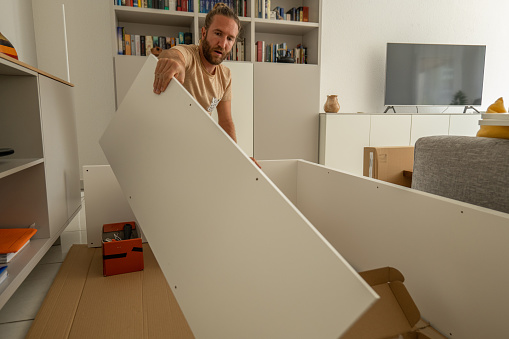 30's man Assembling Wooden Cabinet in Home