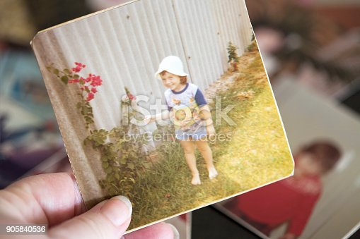 A four year old girl in 1977. Old photograph held in hand while reminiscing. Same model in background photos.
