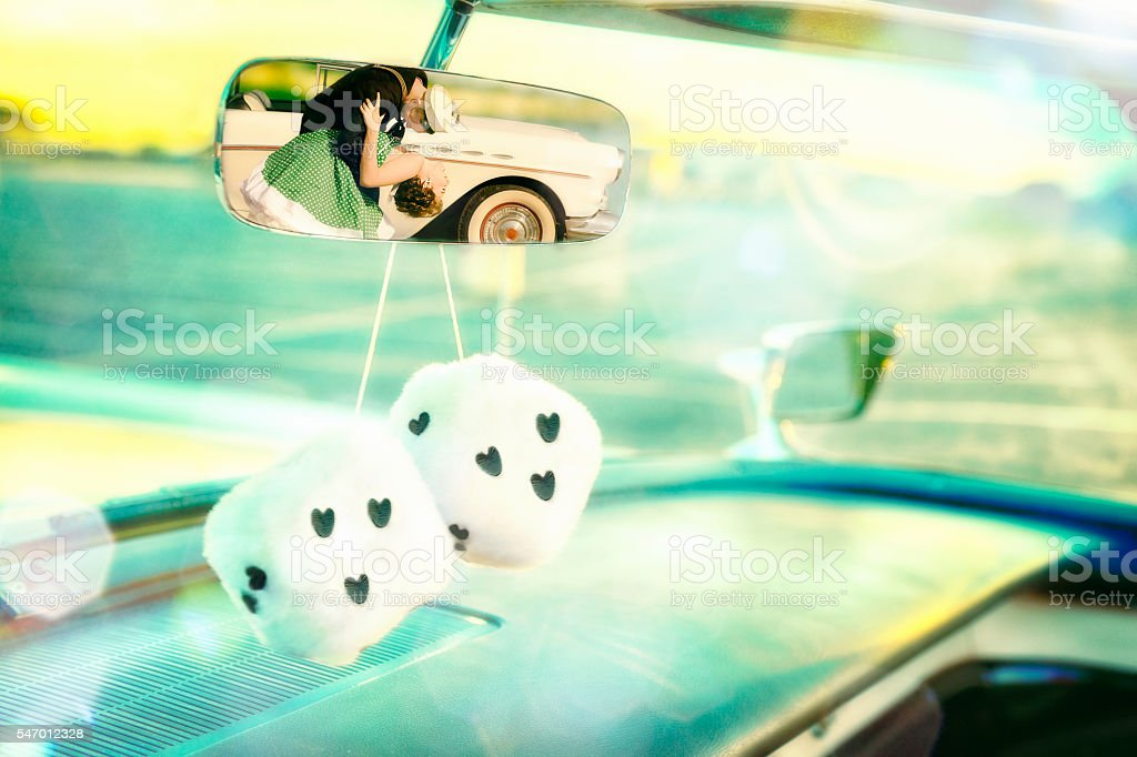 50's Rear View Mirror Couple's Shot With Furry Dice stock photo
