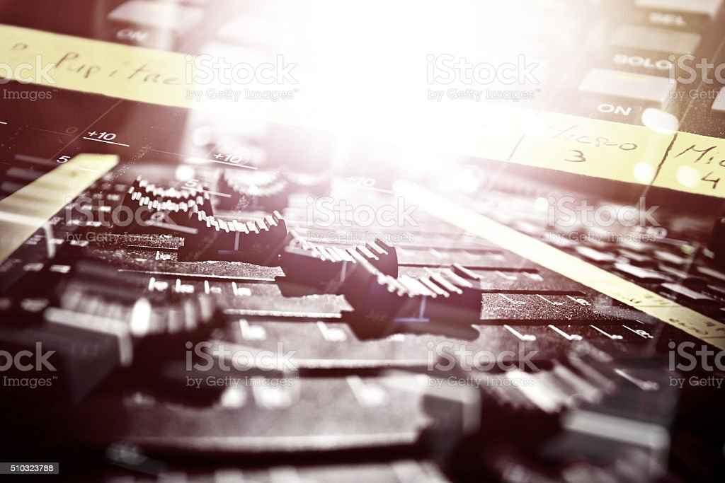 DJ's sound mixer console close-up with lights double exposure effect stock photo