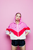 Mid adult beautiful woman wearing oversized tracksuit and shorts standing against pink background, looking at camera.