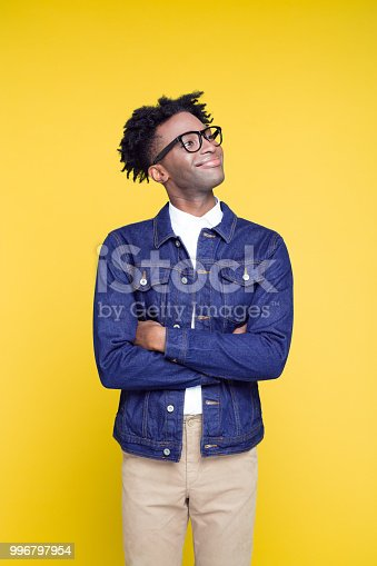 Portrait of happy nerdy young afro American man wearing oversized jeans jacket and glasses, standing against yellow background.
