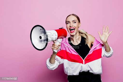 Mid adult beautiful woman wearing oversized tracksuit and shorts standing against pink background, holding megaphone in hands and smiling at camera.