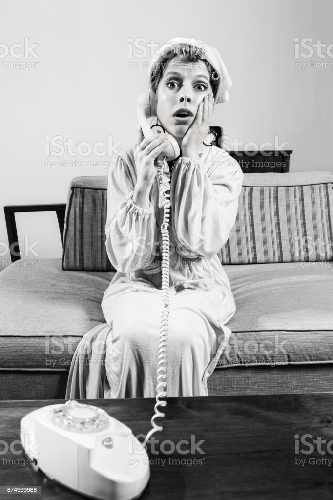 1960's woman gossips on the phone while sitting in her robe stock photo