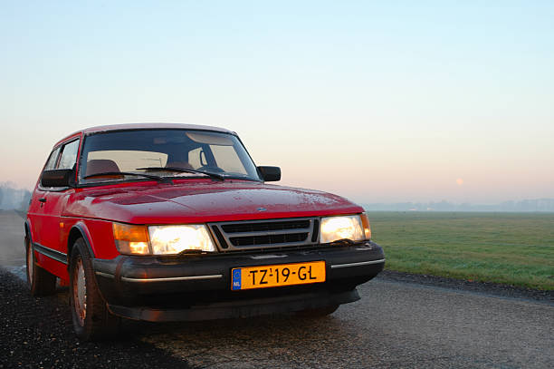 Saab 900 Turbo Kampen, The Netherlands - December 26, 2004: Red Saab 900 Turbo with Dutch license plates is parked next to a road through the country. saab stock pictures, royalty-free photos & images