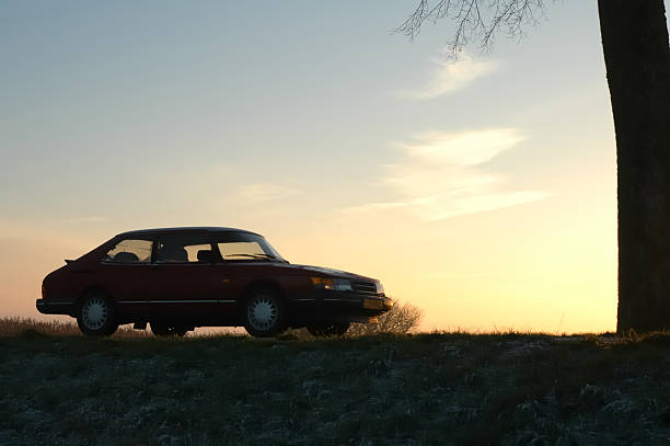 Saab 900 Turbo Kampen, The Netherlands - December 26, 2004: Saab 900 Turbo next to a tree in a sunset on a cold afternoon in winter. saab stock pictures, royalty-free photos & images