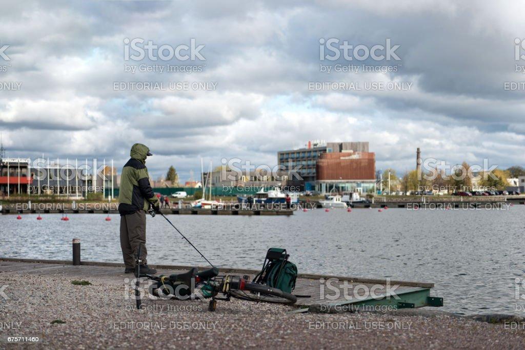 薩列馬、 愛沙尼亞,2014 年 5 月 4 日: 一個人在湖邊釣魚。 免版稅 stock photo