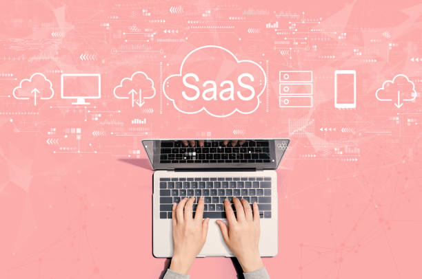 SaaS - software as a service concept with person using laptop stock photo