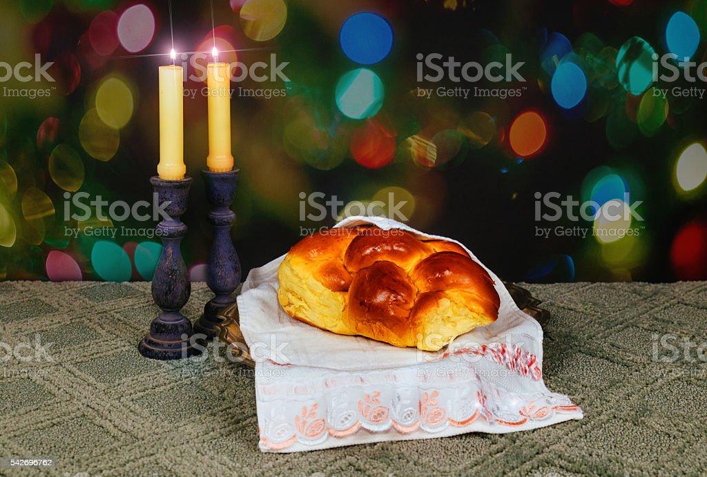 Sabbath image. challah bread, candelas on wooden table. glitter overlay stock photo