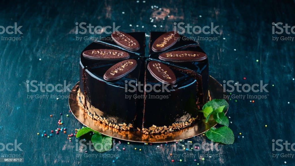 Bolo de Chocolate de Sacher. Sobre um fundo de madeira. Vista superior. Copie o espaço. - Foto de stock de Antigo royalty-free