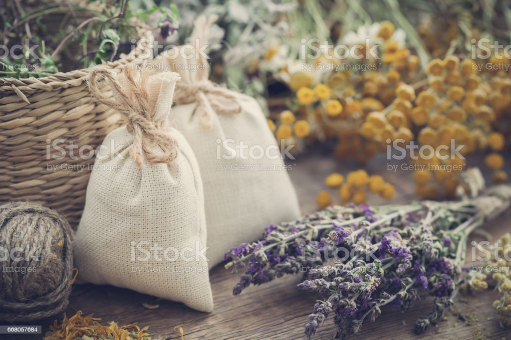 Sachets filled with dried medicinal herbs and bunches of healing...