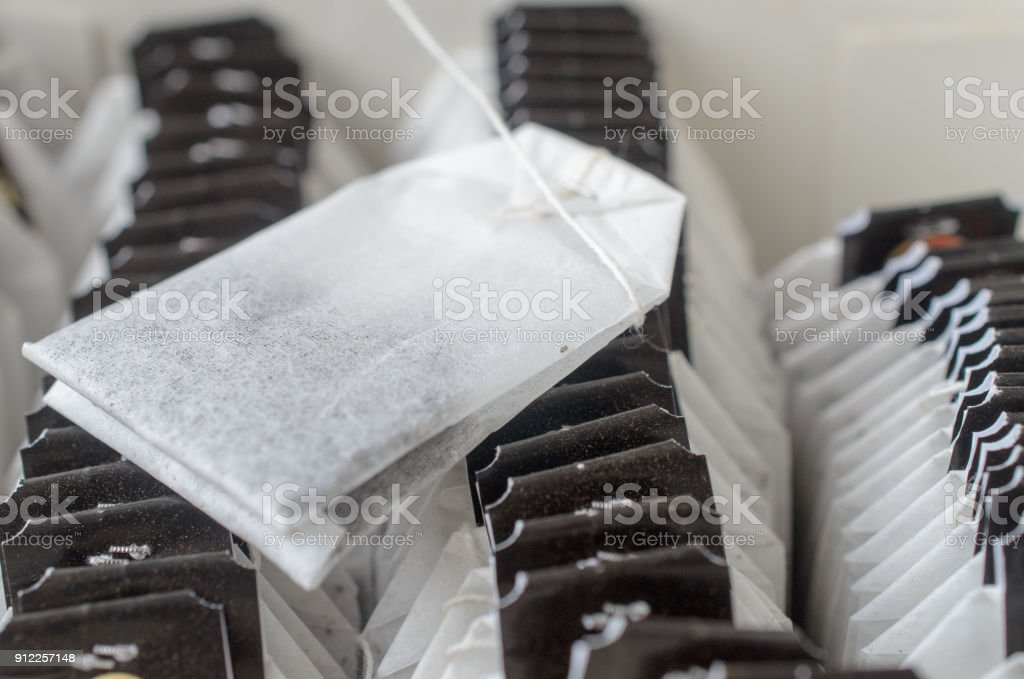 Sachets of black tea with dark tags in the package. stock photo