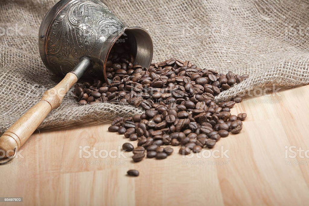 Sackcloth bag with cezve and roasted coffee beans on table royalty-free stock photo