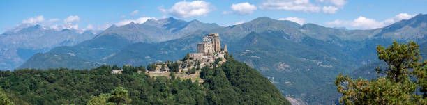 Sacra di San Michele or Saint Michael's Abbey and the alps, Piedmont, Italy. Panoramic view during summer. stock photo