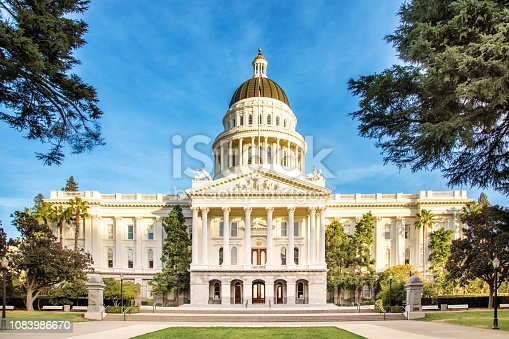 Sacramento California state capitol facade with clear sky and pathway to the entrance staircase.