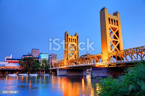 Sacramento, California skyline along the banks of the Sacramento River at night. The Tower Bridge links West Sacramento in Yolo County to the west. Sacramento is the capital city of the U.S. state of California