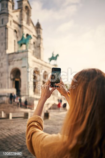 Cropped shot of an unrecognizable woman standing and using a cellphone to take pictures while sightseeing in Paris