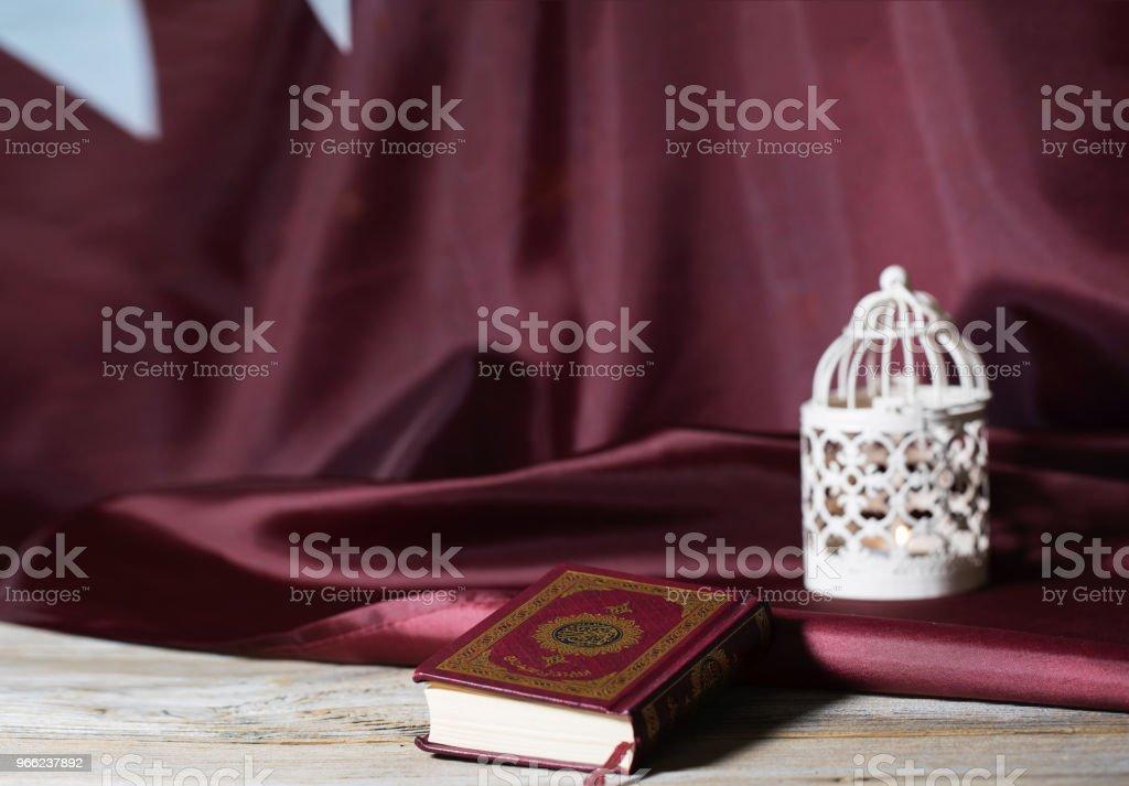 Libro sagrado del Corán en una superficie de madera. Bandera de Qatar y la vela titular en segundo plano. - foto de stock