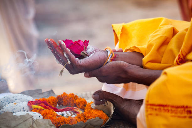 sacred flowers are taken for worship on hand at river ganges - cérémonie photos et images de collection