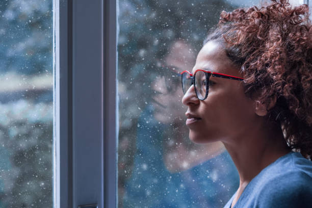Sad african american girl looking out of the window Lonely black woman near window thinking about something and winter snow desolation stock pictures, royalty-free photos & images