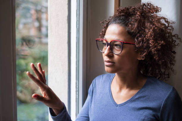 Sad african american girl looking out of the window stock photo