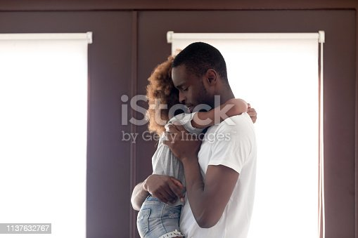 istock Sad African American man holding daughter in hands, saying goodbye 1137632767