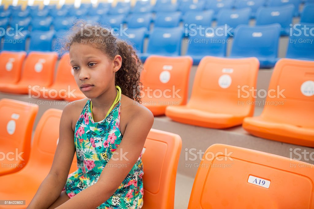 Sad African American teenage girl on a stadium. stock photo