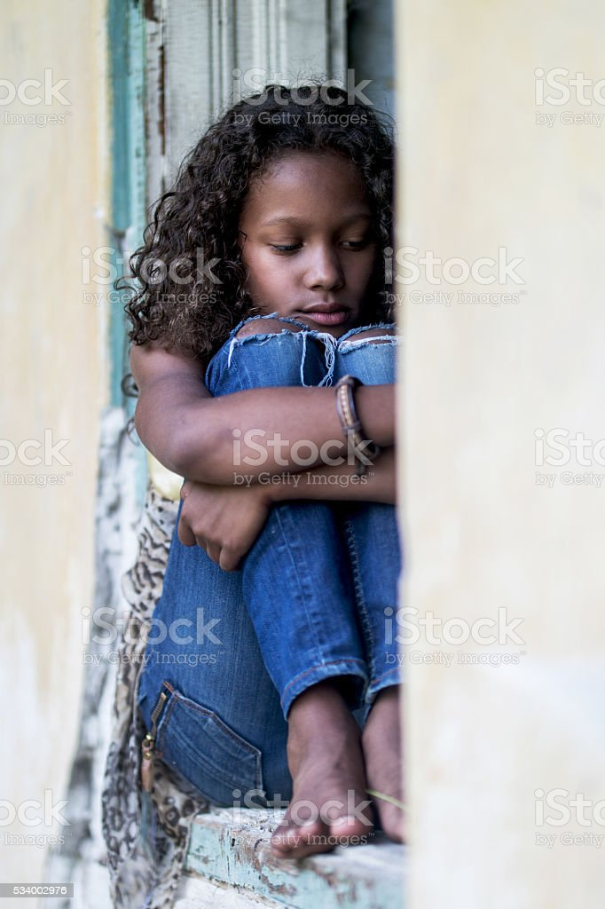 Sad African American teenager sitting on a window frame. stock photo