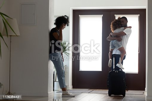 istock Sad african father hugging little daughter before leaving family 1126384431