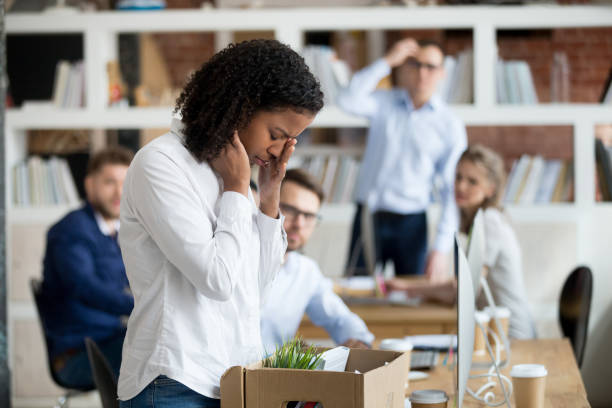 Sad african female employee packing belongings in box got fired Sad african female young employee packing belongings in box at workplace got fired from job, stressed upset black worker intern leaving office on last day at work crying after unfair dismissal downsizing unemployment stock pictures, royalty-free photos & images