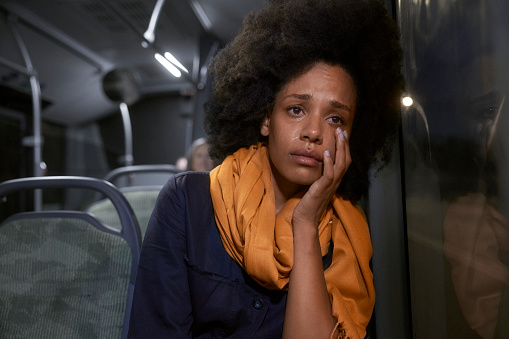 Sad african-american young woman with afro hair sitting on public bus crying wiping tears
