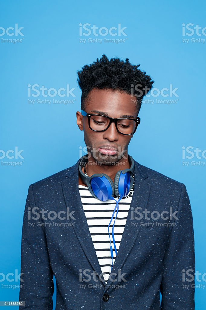 Sad afro american guy in fashionable outfit Studio portrait of sad afro american young man wearing striped top, navy blue jacket, nerd glasses and headphone. Studio portrait, blue background. Adult Stock Photo
