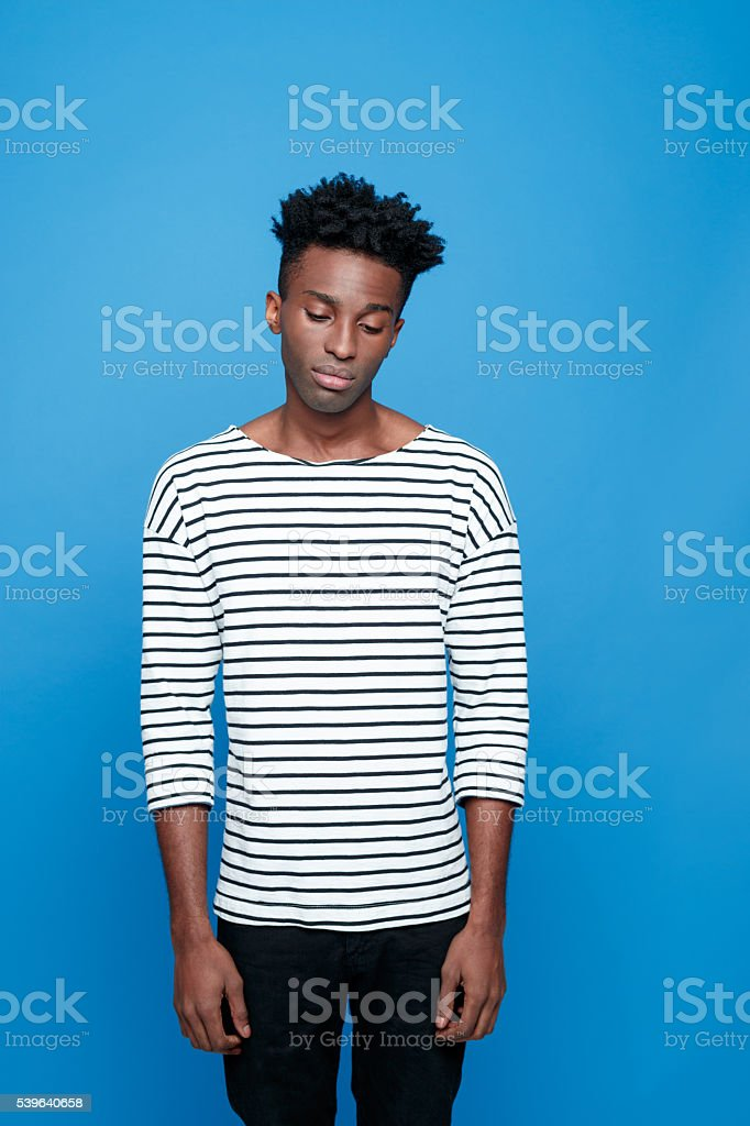 Sad afro american young man Portrait of sad afro american guy wearing striped long sleeved t-shirt. Studio shot, blue background.  Adult Stock Photo