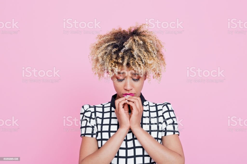 Sad afro american young woman Studio portrait of sad afro american young woman. Pink background. 20-24 Years Stock Photo
