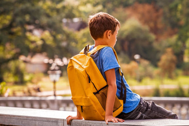 Sad alone boy sitting in the park outdoors Schoolboy sitting outdoors. Back view schoolboy stock pictures, royalty-free photos & images