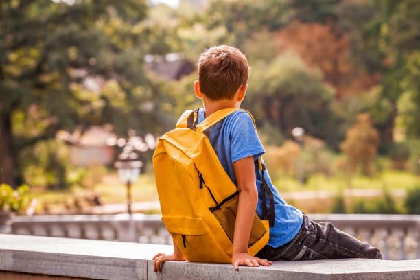 Trauriger, ein junges, der im Park im Freien sitzt – Foto