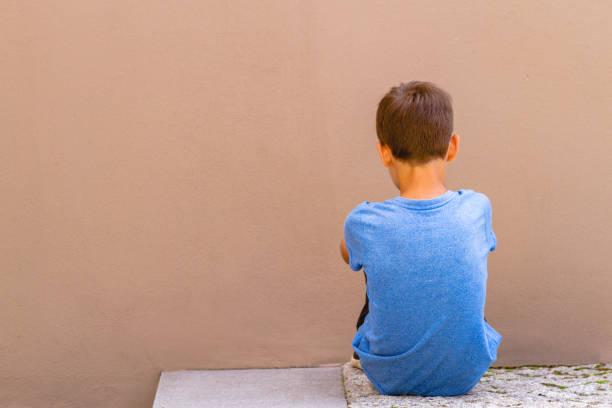 triest alleen jongen zittend op de grond achter de muur buiten - jongen stockfoto's en -beelden