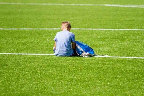 Trauriger allein erbjunger Junge mit Rucksack im Stadion im Freien – Foto