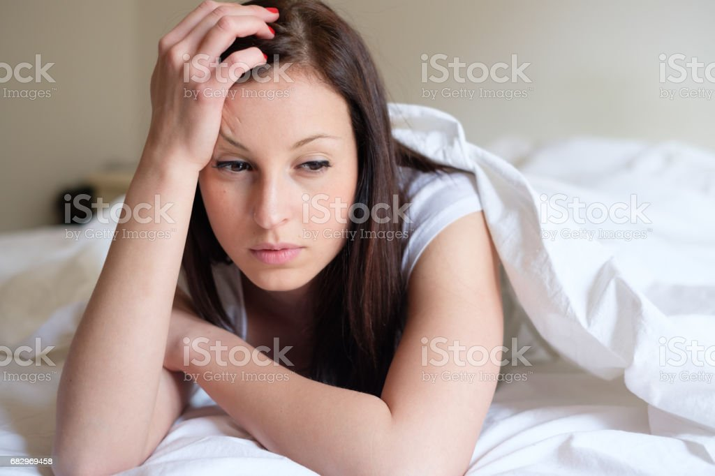 Sad and alone woman lying in her bed stock photo