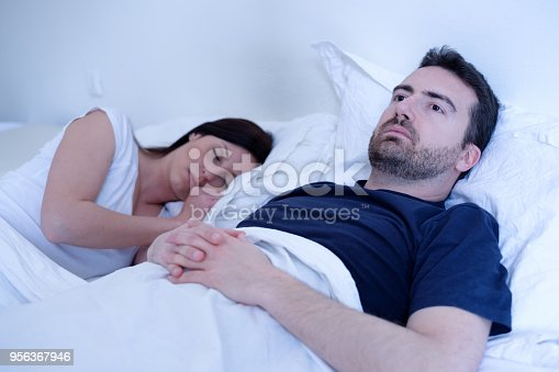 683664728istockphoto Sad and depressed man lying in the bed with wife 956367946