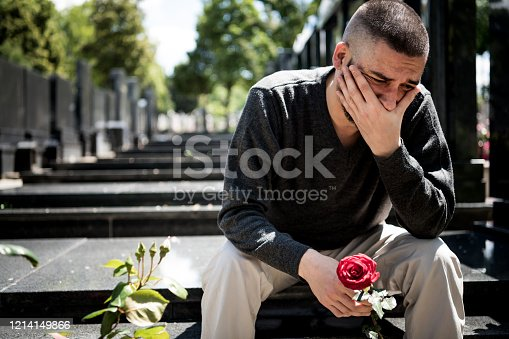 Desperate Bearded Man is Sitting on the Tombstone with a Flower and Mourning over his Loss. Mature Man is Feeling Sad while Sitting at the Graveyard and Crying Because of Unhappiness he is Going Through.