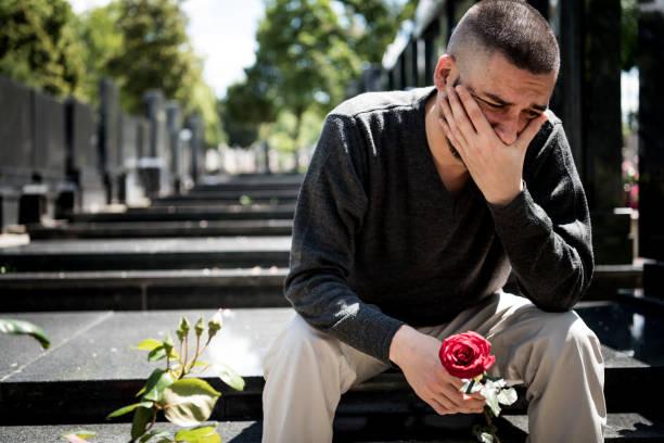 Veuve triste et déprimée dans les vêtements noirs agenouillés devant la pierre tombale, tenant une fleur et gémit pour la perte de famille. Concept pour la mort, le deuil, les funérailles et la spiritualité.- Covid-19 - Photo