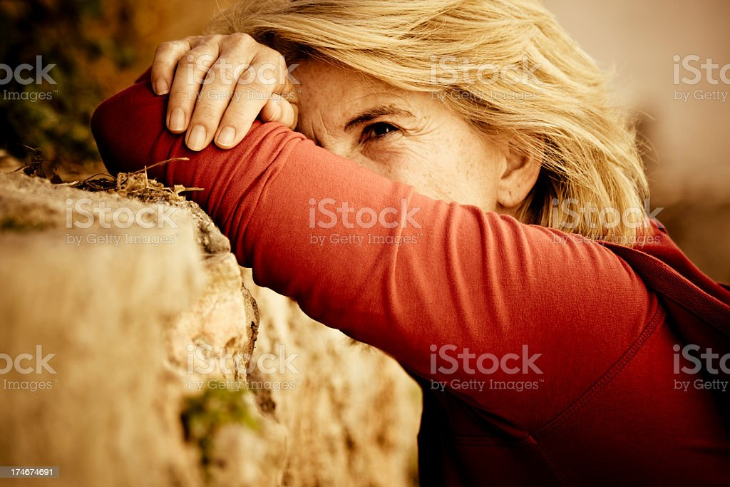 Sad and desperate woman leaning on rock in sepia royalty-free stock photo