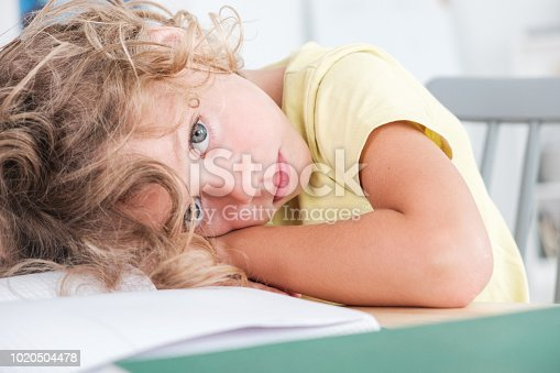 istock Sad and lonely kid lying his head on a desk 1020504478