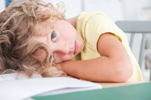 Sad and lonely kid lying his head on a desk stock photo