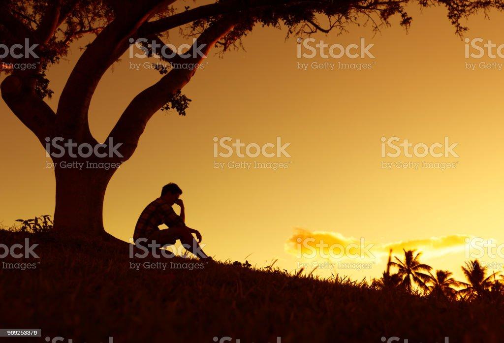 Sad and lonely man sitting alone under a tree. – zdjęcie