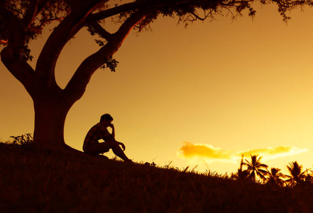 Sad and lonely man sitting alone under a tree. stock photo