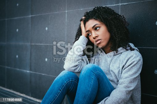 Sad and lonely girl portrait in the urban street